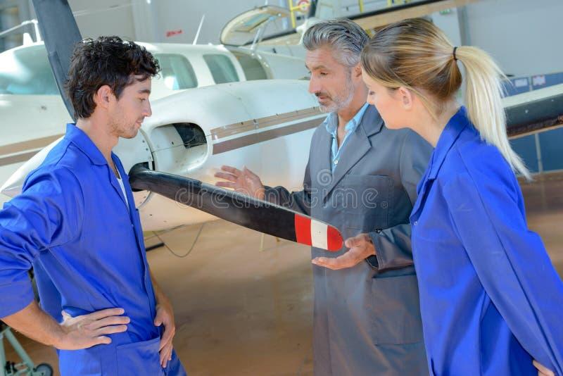Aviation students looking at propellor aircraft royalty free stock image