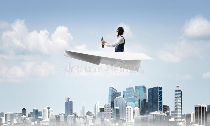 Aviator driving paper plane above business center stock photography