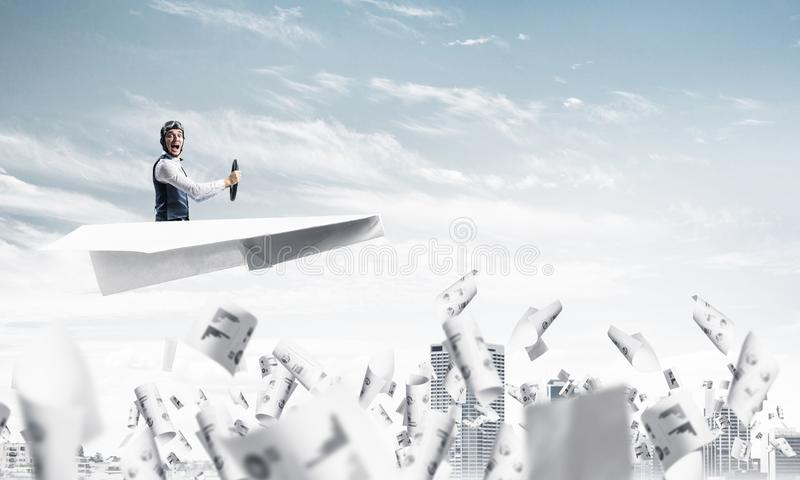 Aviator driving paper plane above business center. In blue sky. Working with business documentation. Papers falling down on background of skyscrapers. Pilot in royalty free stock images