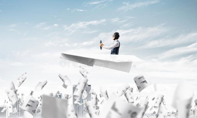 Aviator driving paper plane above business center. In blue sky. Working with business documentation. Papers falling down on background of skyscrapers. Pilot in royalty free stock photo