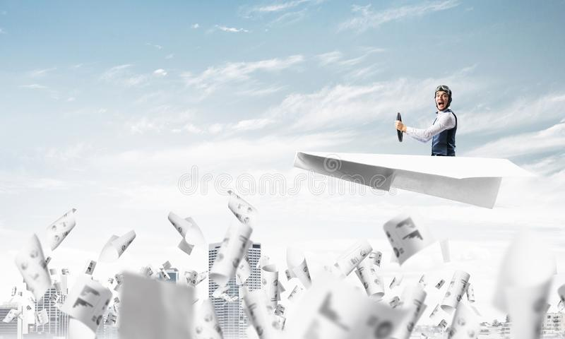 Aviator driving paper plane above business center. In blue sky. Working with business documentation. Papers falling down on background of skyscrapers. Pilot in royalty free stock photos