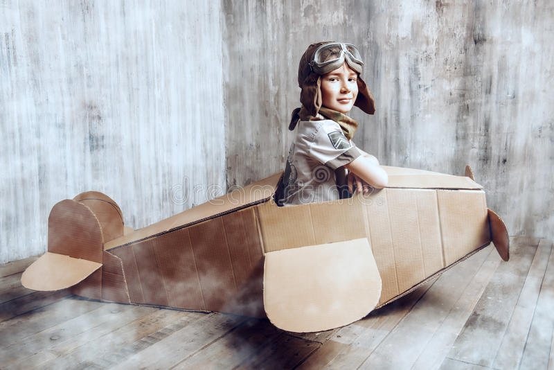Aviator. Little dreamer boy playing with a cardboard airplane. Childhood. Fantasy, imagination stock photos