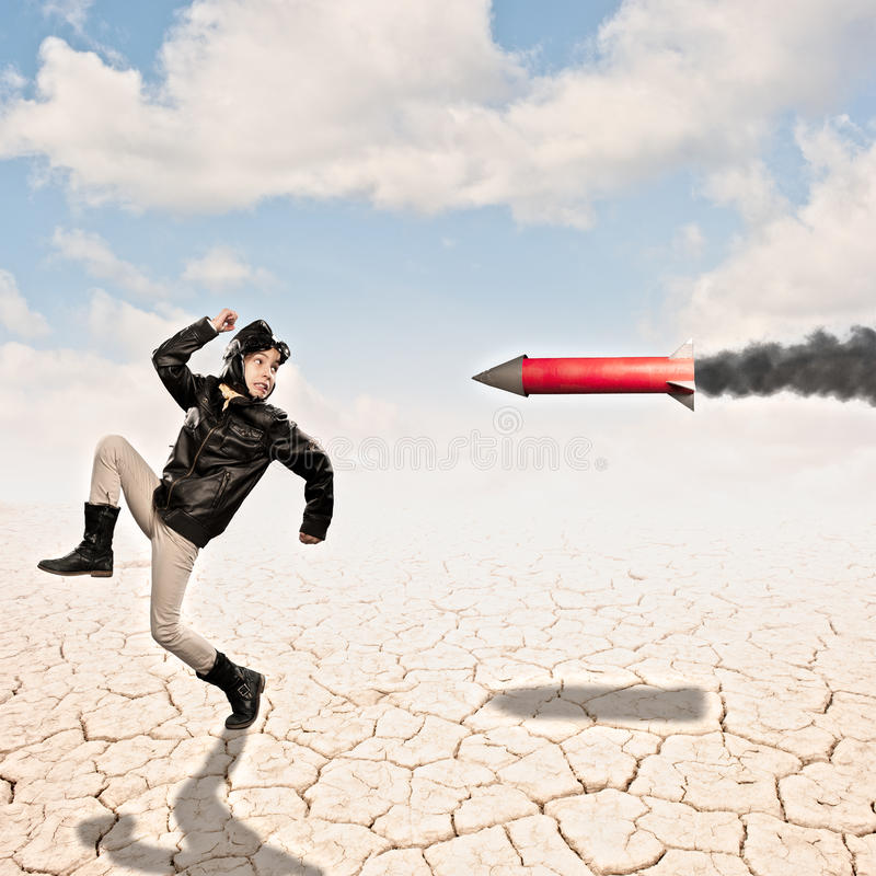 Aviator with a rocket in hot pursuit. Little aviator with a rocket in hot pursuit at the desert royalty free stock photo