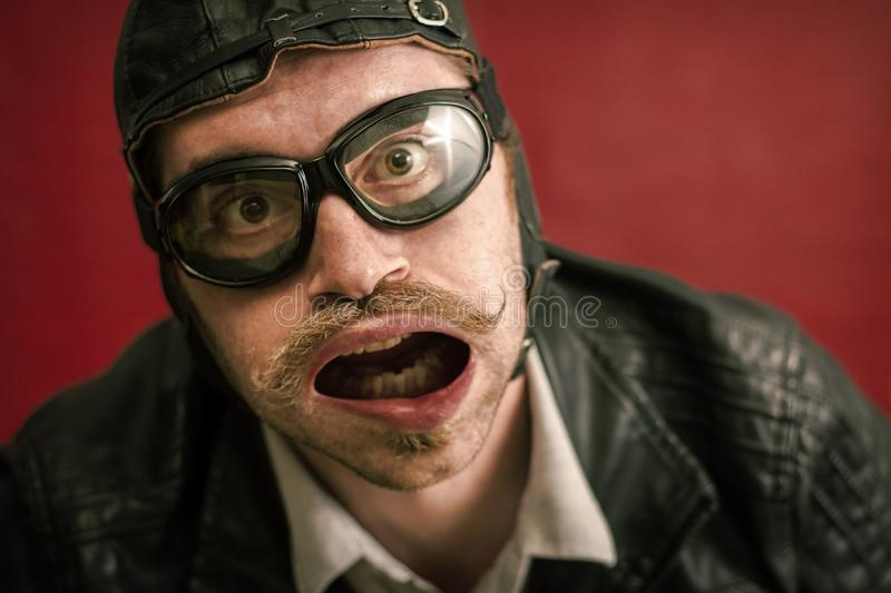 Aviator Silly Expression. Man wearing aviator hat and goggles makes silly facial expression from strong wind stock image