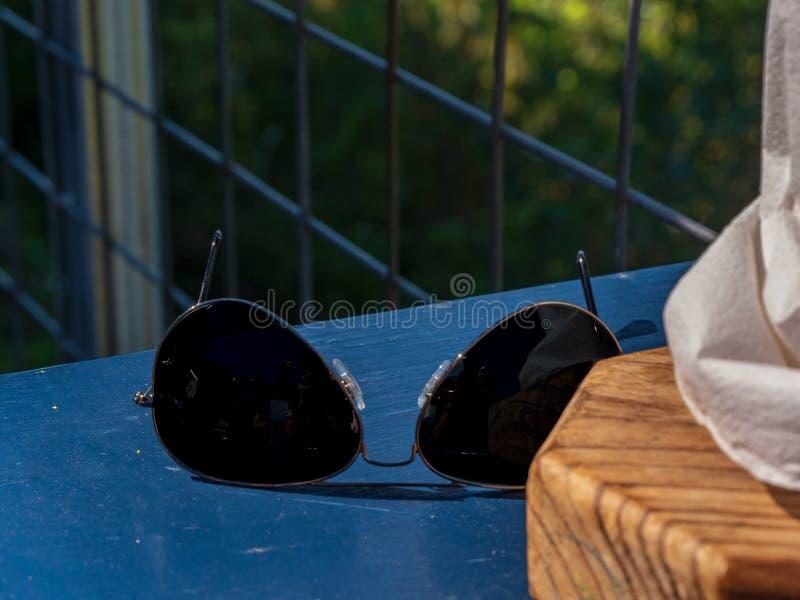 Aviator style sunglasses on table royalty free stock photos