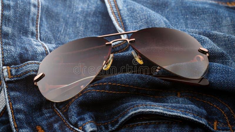 Aviator sunglasses on blue jeans, Devon, United Kingdom, October 5, 2018. Aviator sunglasses on blue jeans, Devon, United Kingdom royalty free stock photo