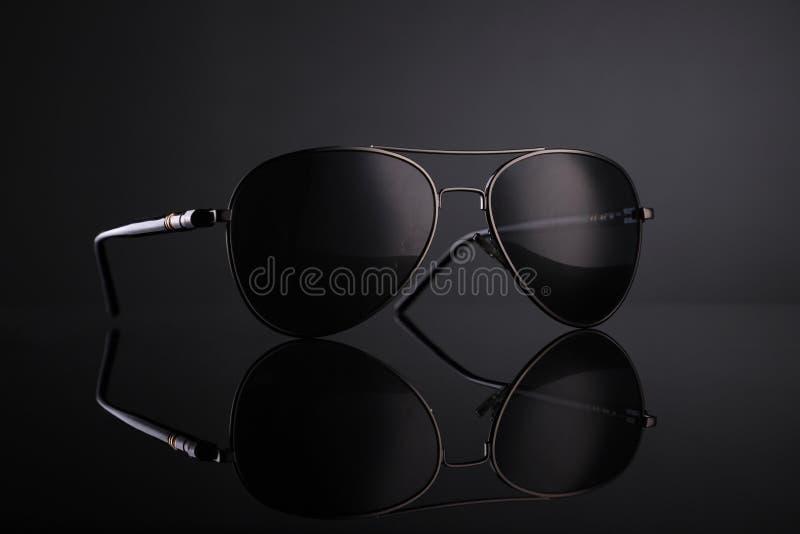 Aviatore nero Sunglasses su fondo nero con la riflessione fotografia stock