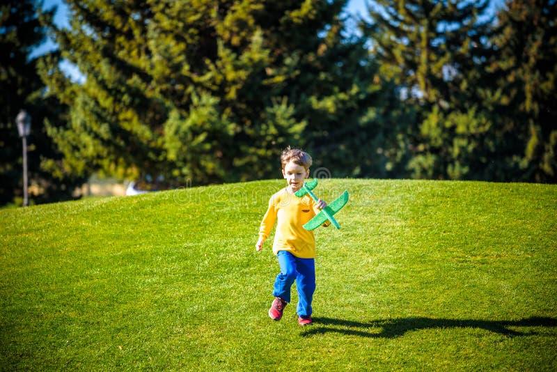 Aviatore pilota del bambino con i sogni dell'aeroplano di viaggio di estate in natura al tramonto fotografie stock libere da diritti