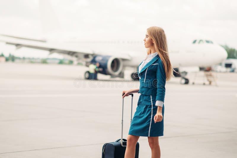 Προκλητική αεροσυνοδός με τη βαλίτσα στο χώρο στάθμευσης αεροσκαφών στοκ εικόνες