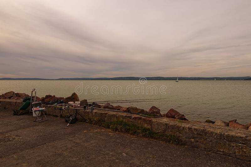 Avid fisherman fishing spot. Fishing tackle on a pier on the background of the lake Balaton. Vibrant sky in cloudy day. stock photo