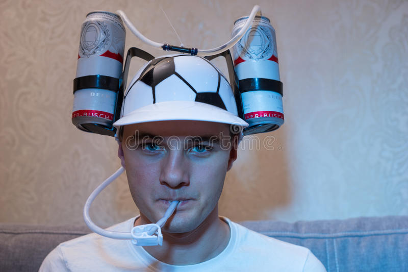 Avid football supporter in a goofy hat. Shaped like a football with flasks of liquid on either side and a tube to his mouth for refreshment and hydration glued stock photography