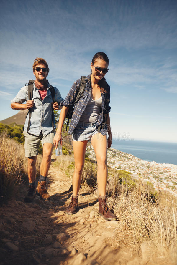 Avid hikers in countryside. Portrait of couple of happy hikers walking in the countryside. Young caucasian men and women hiking on a summer day stock images