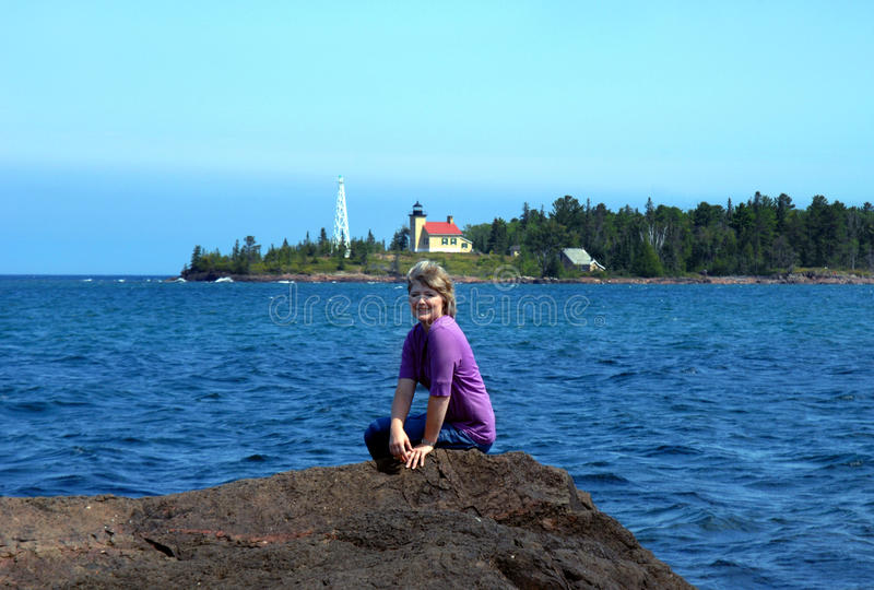 Avid Lighthouse Lover. Attractive woman poses on the rocky shoreline of Lake Superior. In the background is the Copper Harbor Lighthouse and Lighthouse Keepers stock image