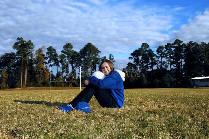 Avid School Fan. Female high school student sits in the middle of the football field. She is hugging a helmet and wearing her school colors. She exhibits school stock photos