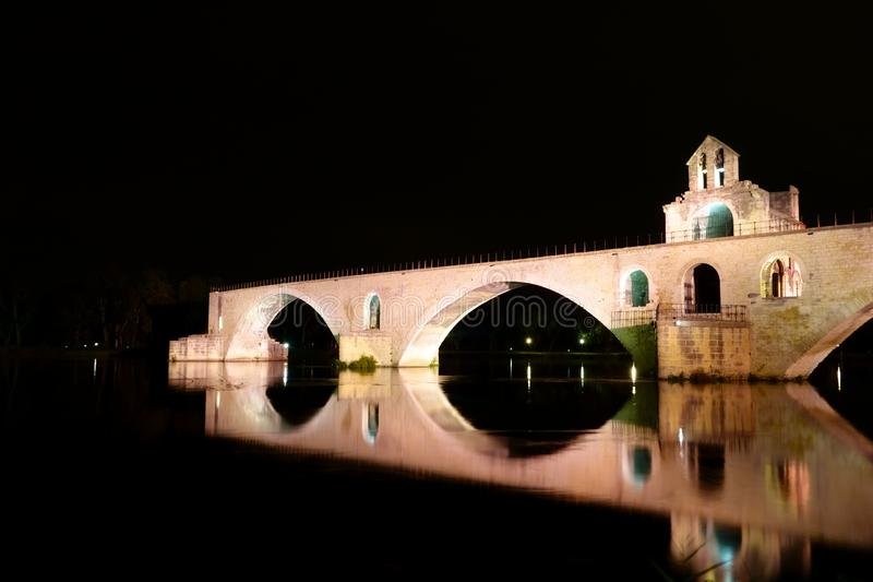 Brightly illuminated bridge Pont d`Avignon in pink color stock image