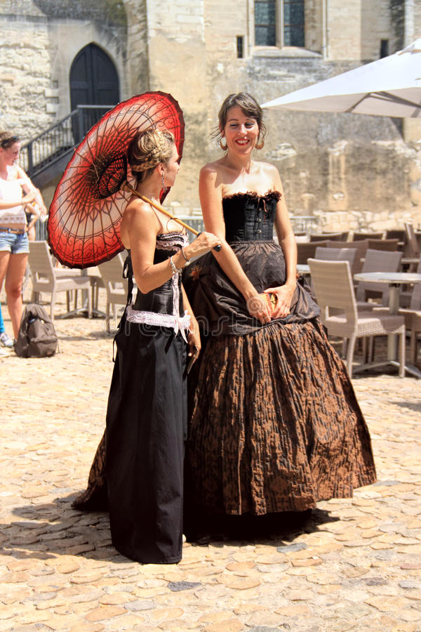 Avignon Theatre Festival. AVIGNON, FRANCE – JULY 19, 2014: Two actresses in historical costumes advertising their performance in front of the Papal Palace stock images