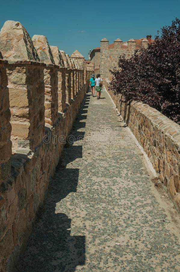 People walking on pathway over wall with leafy tree at Avila. Avila, Spain - July 23, 2018. People walking on pathway over stone thick wall with leafy tree at royalty free stock photo