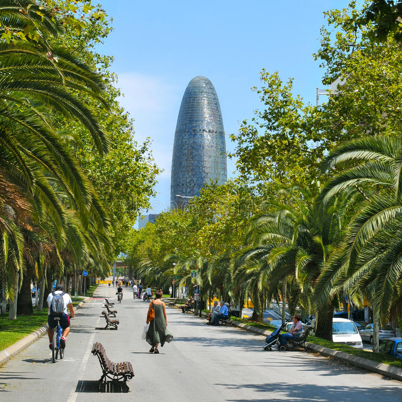 Avinguda Diagonal and Torre Agbar in Barcelona, Spain. BARCELONA, SPAIN - JULY 14: People walking in Avinguda Diagonal with the Torre Agbar in the background on royalty free stock images