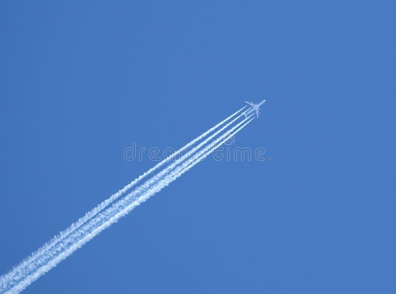 Avion à réaction dans le ciel bleu avec une voie inverse images stock