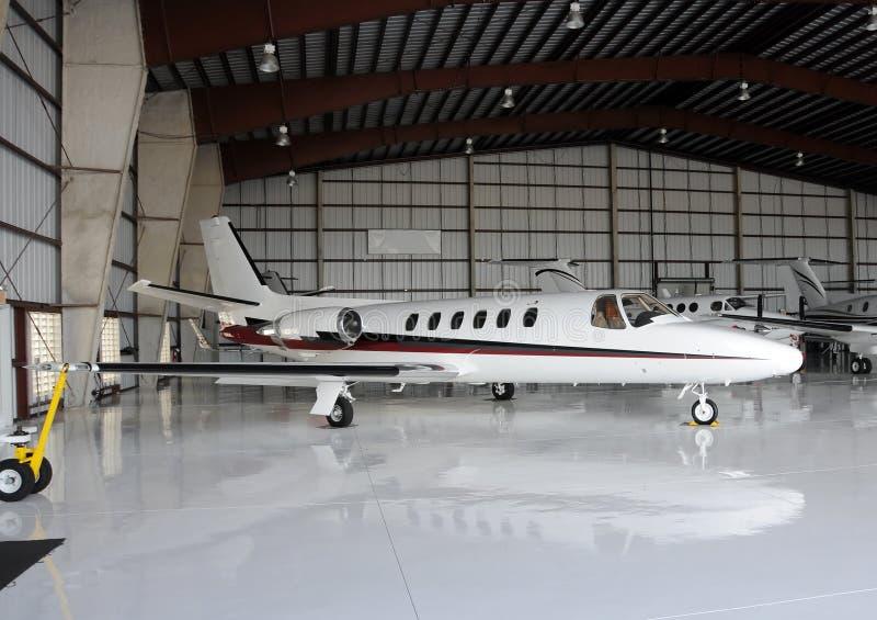 Avion à réaction privé dans le hangar images stock