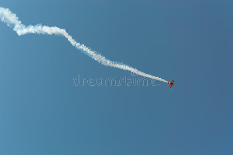 Avion acrobatique aérien laissant une traînée blanche de fumée dans le ciel bleu photo libre de droits