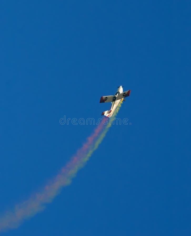 Avion avec de la fumée colorée image stock
