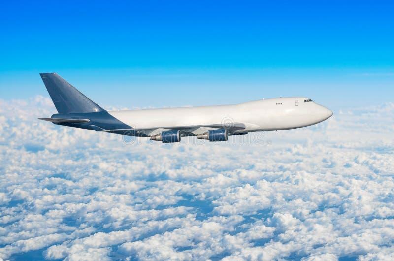 Avion avec quatre moteurs, camion sans hublots dans le ciel au-dessus de la taille du soleil de voyage de vol de nuages images libres de droits