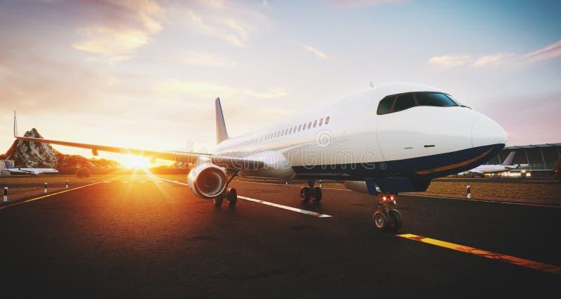 Avion commercial blanc se tenant sur la piste d'aéroport au coucher du soleil La vue de face de l'avion de passager décolle illustration stock
