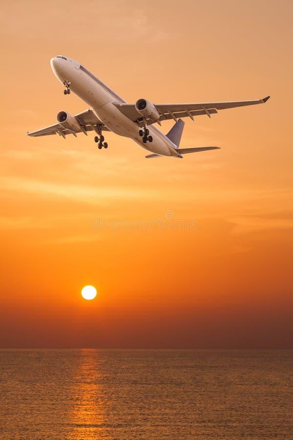 Avion commercial volant au-dessus de la mer photographie stock libre de droits