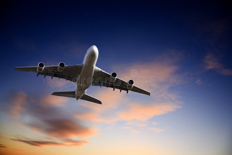 Avion d'avion à réaction décollant dans le ciel crépusculaire lumineux image libre de droits