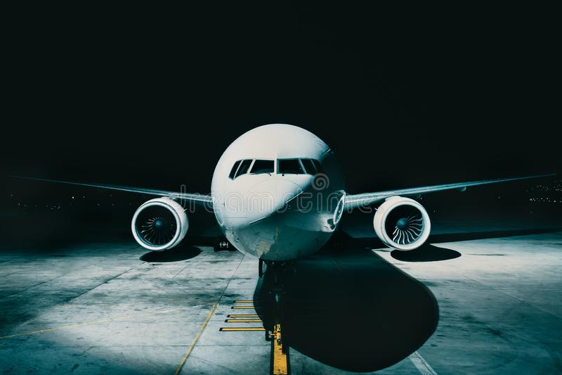 Avion d'avion de ligne garé à la vue terminale du fuselage avant d'habitacle, sur la piste la nuit photo stock