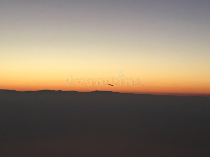 Avion dans la distance avec le coucher du soleil photos libres de droits