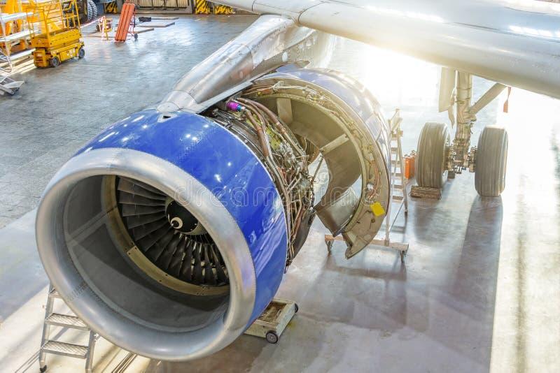 Avion dans le hangar pour l'entretien, vue de l'aile de moteur avec le capot ouvert photographie stock libre de droits