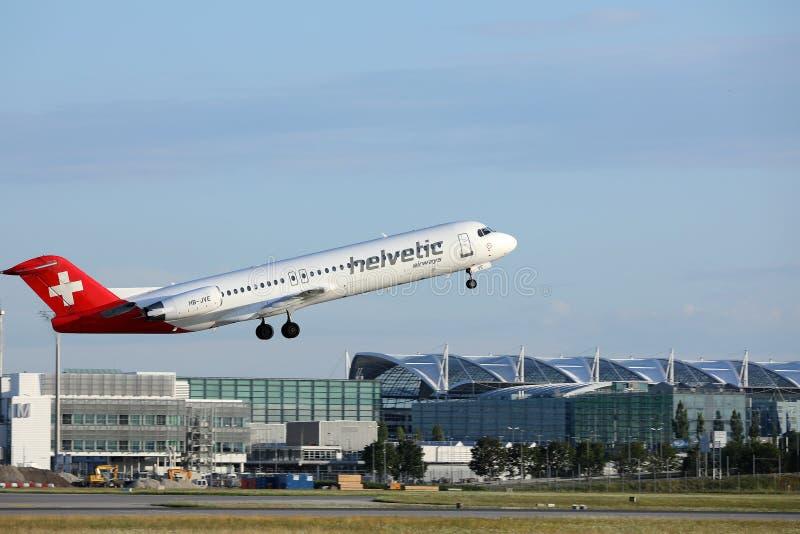 Avion de Helvetic Airways décollant de l'aéroport de Munich images stock