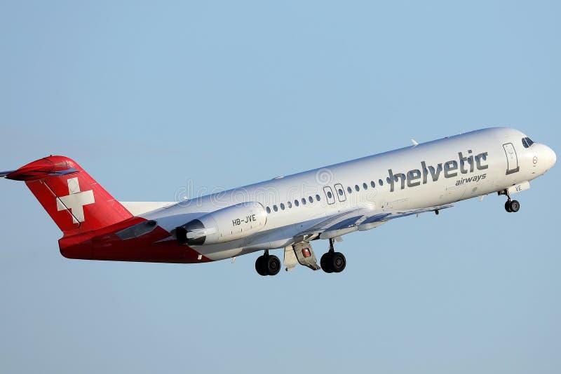 Avion de Helvetic Airways décollant de l'aéroport de Munich photographie stock libre de droits