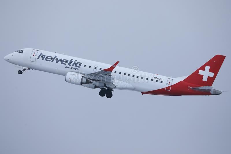 Avion de Helvetic Airways volant dans le ciel image libre de droits