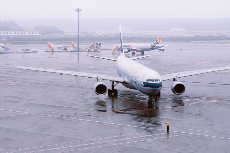 Avion de la compagnie aérienne Cathay Pacific Airline pendant les pluies du mauvais temps à l'aéroport international de Tokyo Nar photos stock