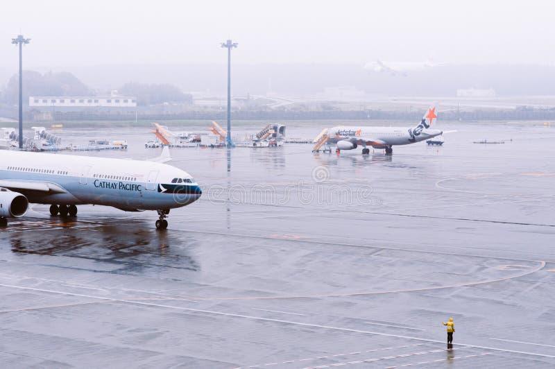 Avion de la compagnie aérienne Cathay Pacific Airline pendant les pluies du mauvais temps à l'aéroport international de Tokyo Nar image libre de droits