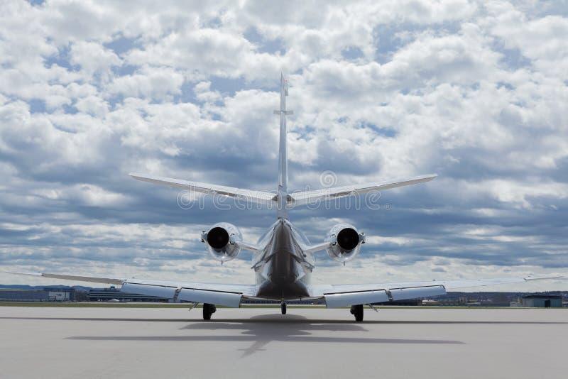 Avion de learjet d'avions devant l'aéroport avec le ciel nuageux photos libres de droits