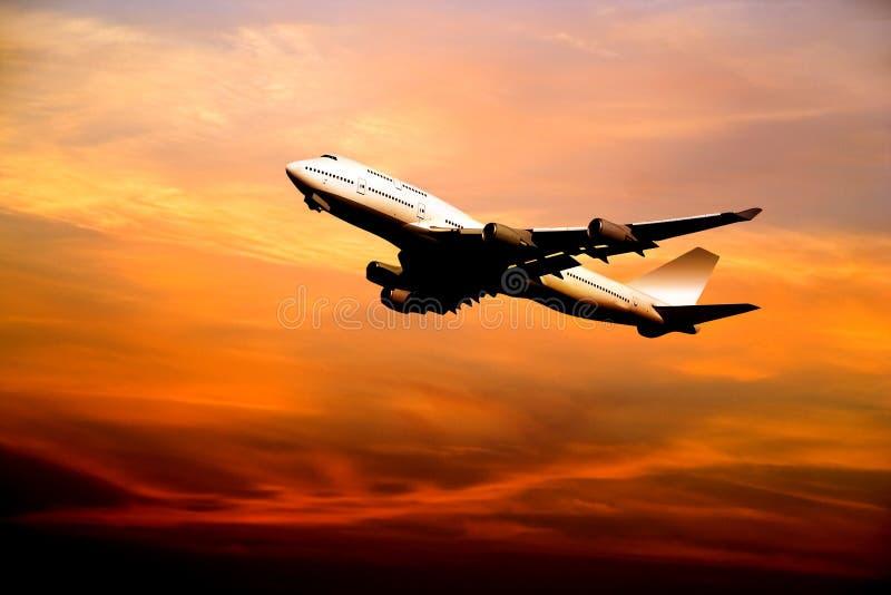 Avion de ligne décollant au coucher du soleil images stock