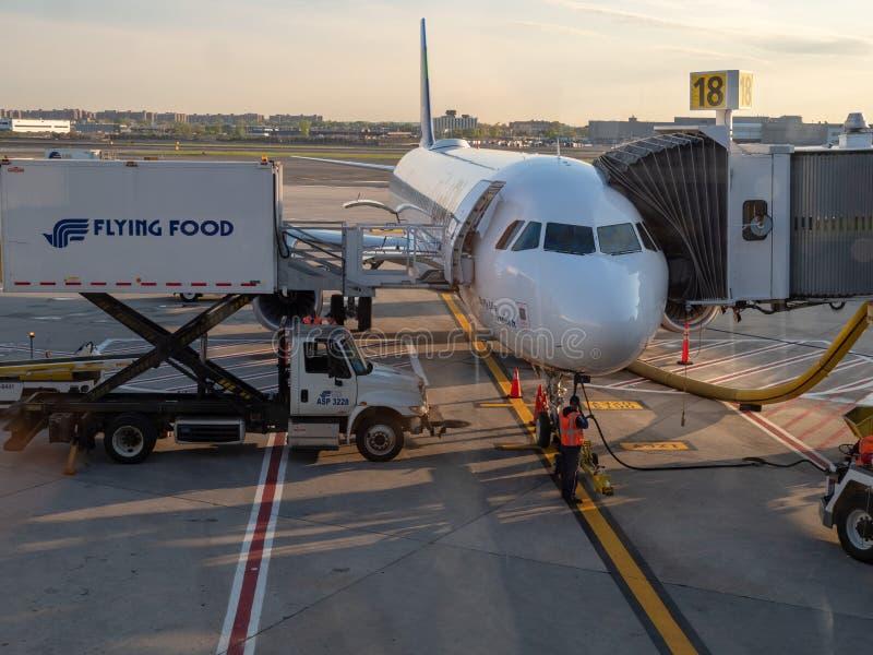 Avion de ligne de JetBlue complétant le niveau avec les approvisionnements et le carburant à l'airp de JFK photographie stock