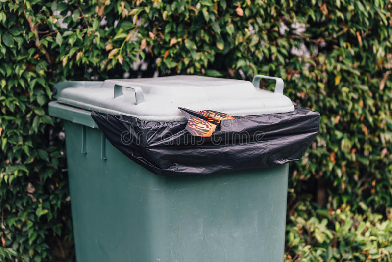 Avion de papier coloré débarqué au-dessus de la poubelle verte photographie stock