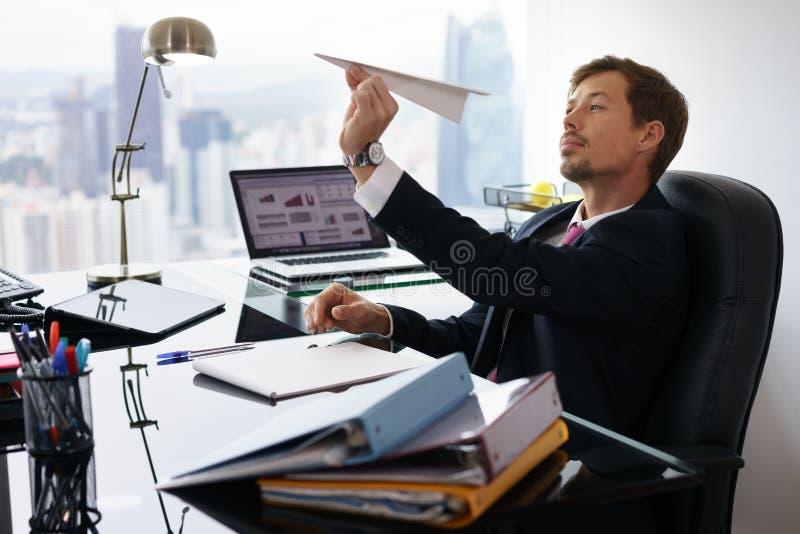 Avion de papier de lancement ennuyé de travailleur intellectuel dans le bureau photo stock
