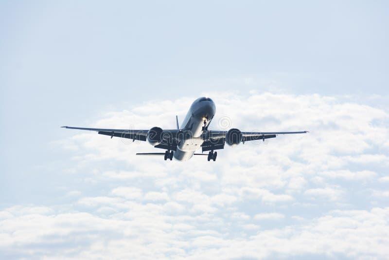 Avion de passager passe-bas sur le ciel images stock