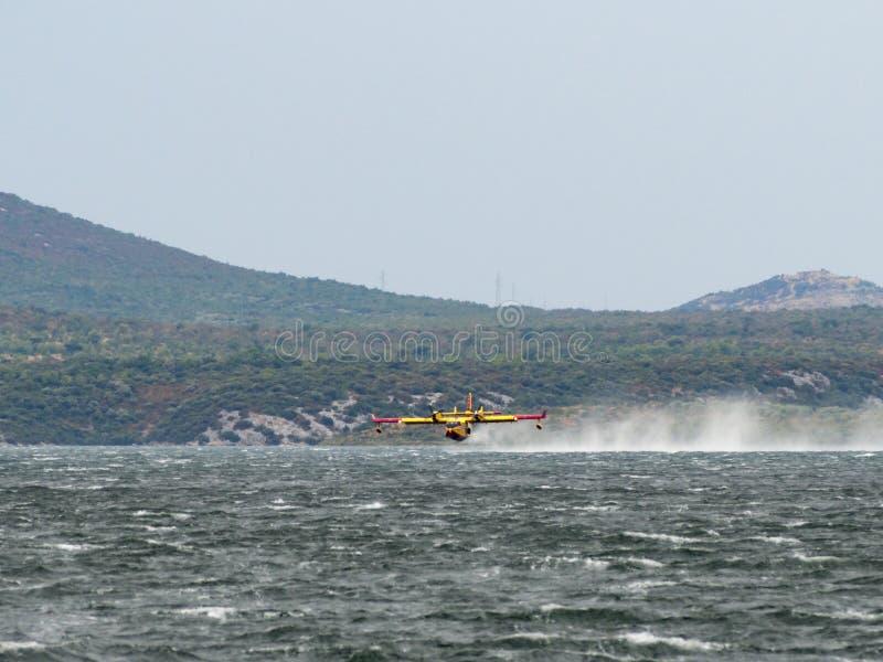 Avion de sapeur-pompier, bombardier de l'eau, réservoir d'air prenant l'eau de t photographie stock
