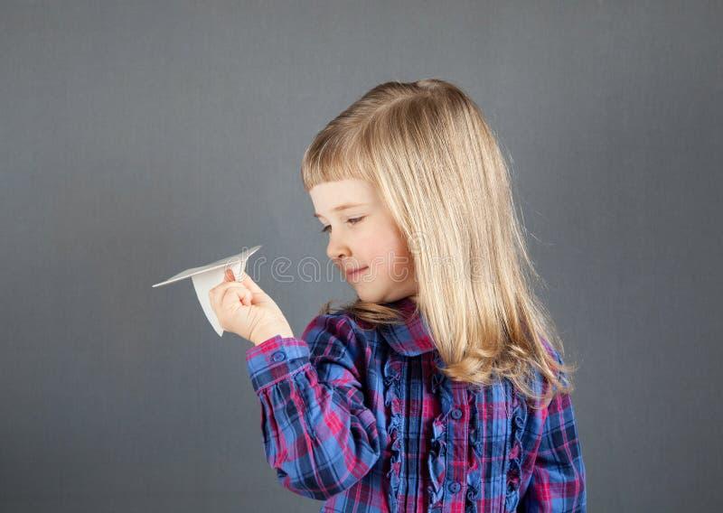 Avion de sourire de papier de vol de petite fille photographie stock