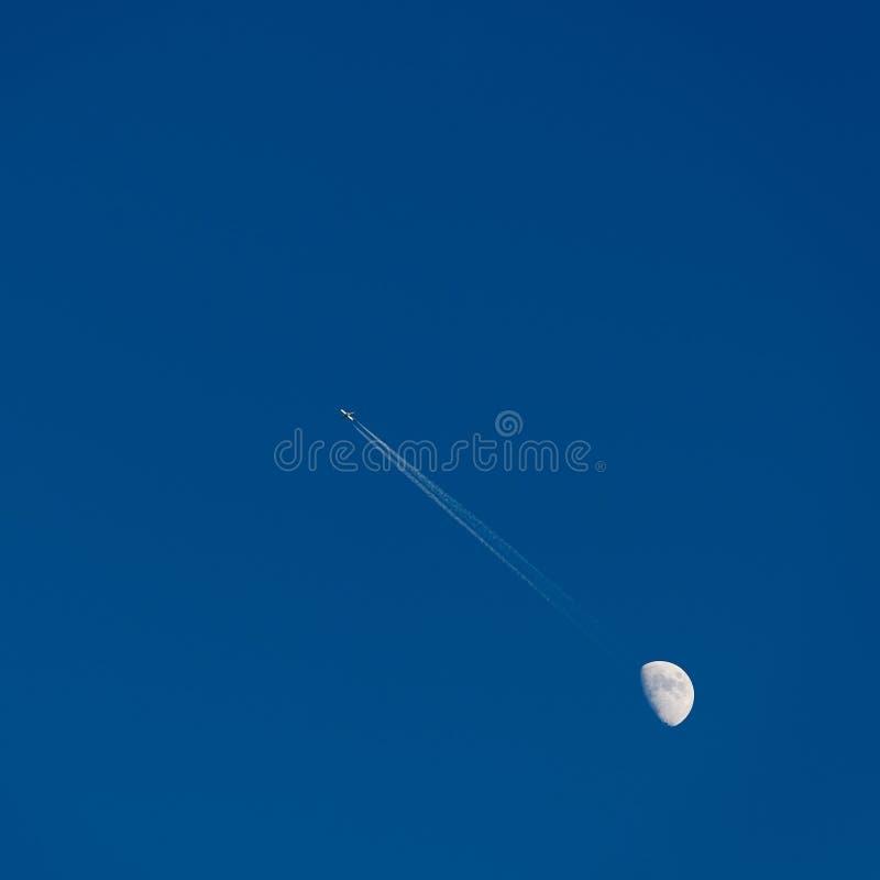 Avion et lune dans le ciel photographie stock