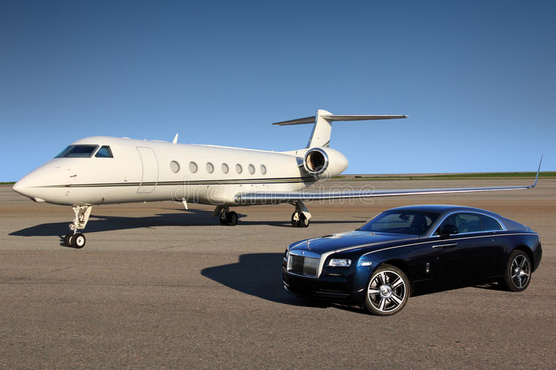 Avion exécutif privé de Gulfstream G550 avec la voiture de luxe de Rolls Royce Wraith montrée ensemble à l'aéroport international images libres de droits