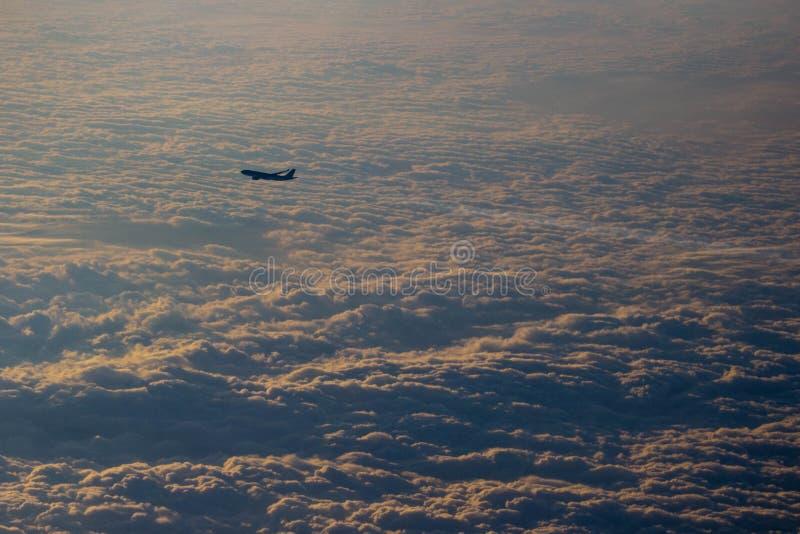 Avion laissant un contrail vu d'un autre avion sur un tapis déprimé des nuages pendant le coucher du soleil image stock