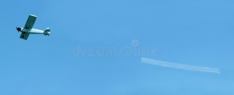 Avion remorquant le drapeau blanc photo stock
